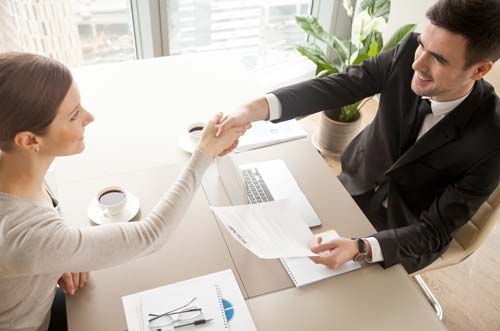 Executive shaking hands with hiring manager after working with headhunter (source: freepik.com)